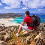 Mies istuu reppu selässä korkealla kalliolla ja ihailee merta.