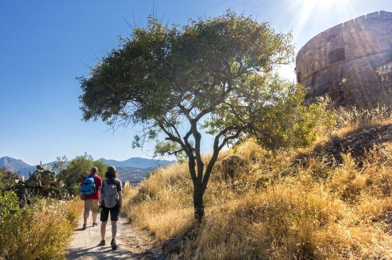 Kaksi ihmistä reput selässä kulkee polkua vanhan linnoituksen vierellä.
