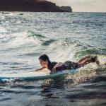 Teini-ikäinen nuori makaa surffilaudan päällä pienessä aallossa