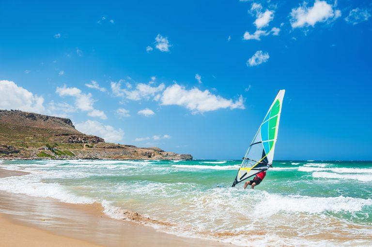 Mies ohjaa purjelautaa rannan suuntaisesti aurinkoisessa säässä.