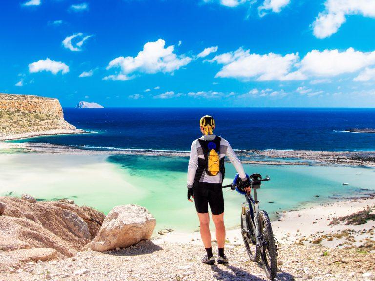 Henkilö seisoo pitäen kiinni maastopyörästä ja ihailee merimaisemaa.