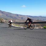 Kaksi henkilö ajaa maastopyörillä peräkkäin alas mutkaista asfalttitietä.