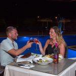 Pariskunta illallisella altaan edustalla