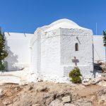 Vanhan valkoisen luostarin julkisivu, johon aseteltu puinen risti.