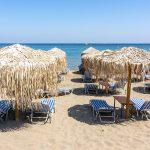 Falirakin rannalla sinivalkoisia aurinkotuoleja ja kaislakattoisia aurinkovarjoja.