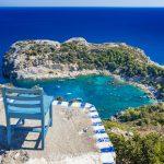 Sininen tuoli asetettuna korkealle betonitasanteelle, josta näkymä alas rannalle ja poukamaan.