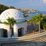 Palmujen ympäröimä kupolikattoinen valkoinen rakennus rannan tuntumassa.