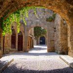 Keskiaikainen kuja, muuratun kaaren takaa roikkuu köynnöksiä.