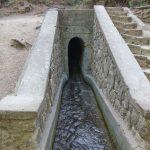 Vesi virtaa kapeaan tunneliin maan alle.