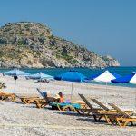 Ihmisiä aurinkopedeillä rannalla sinivalkoisten päivävarjojen alla.