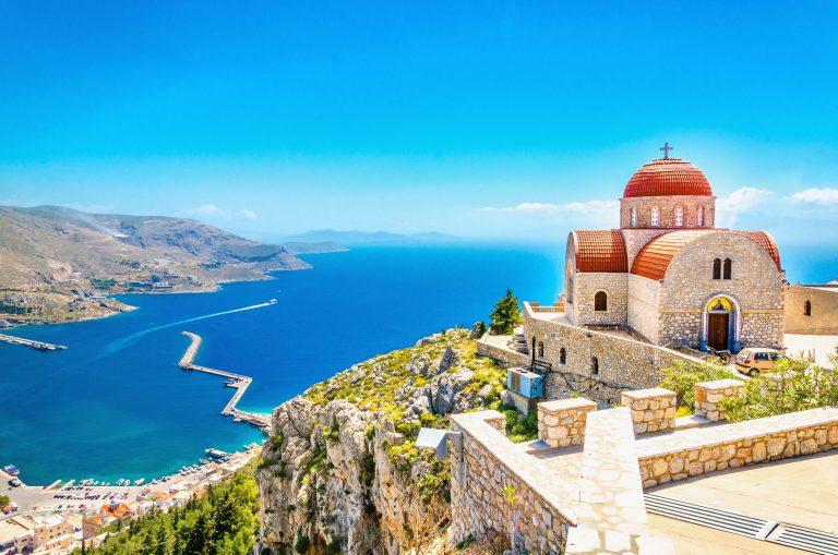 Näkymä kallioiselta kukkulalta merelle tasanteella olevan kivisen kirkon takaa.