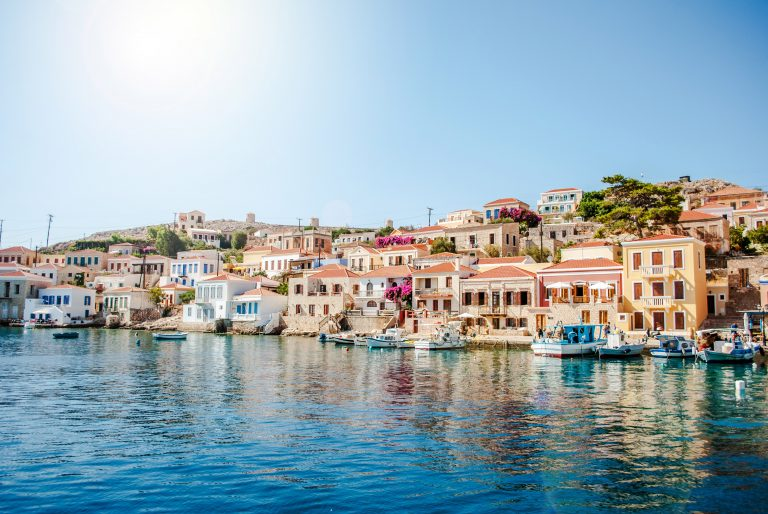 Loivassa rinteessä olevia rakennuksia sekä rantaan kiinnitettyjä veneitä mereltä päin kuvattuna.