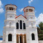 Valkoisen Agios Nikolaoksen kirkon julkisivu aurinkoisena päivänä, taustalla meri.