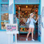 Hattupäinen hymyilevä nainen siniseksi maalatun matkamuistomyymälän ovella katsomassa tuliaisia.