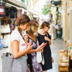 Kolme naista matkapuhelimet kädessä katsomassa kadulla myytäviä matkamuistoja.