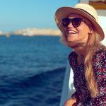 Hattupäinen nainen aurinkolasit päässä hymyilee leveästi ja ihailee merta veneen kyydissä.