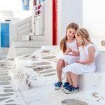 Kaksi pientä tyttöä valkoiset mekot päällä istuvat portailla kreikkalaisella kujalla.