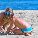 Kaksi lasta kaivaa hiekkaa kreikkalaisella rannalla.