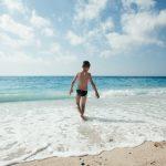 Pieni poika kävelee rantavedessä aurinkoisessa säässä kreikkalaisella rannalla.