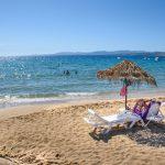 Ihmisiä uimassa kimmeltävässä meressä ja kaksi naista lukemassa aurinkovarjojen alla hiekkarannalla.