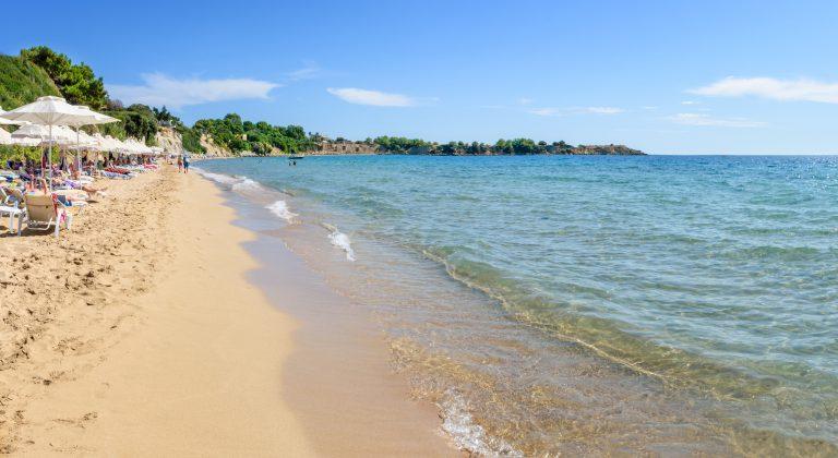 Ihmisiä ottamassa aurinkoa ja kävelemässä hiekkarannalla turkoosin meren äärellä.