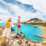 Pariskunta katsoo mäeltä alas rannalle, naisella kädessään Kreikan lippu.
