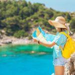 Nainen lierihattu päässään ja keltainen reppu selässään katsoo karttaa meren äärellä.