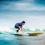 Nuori poika surffilaudalla pienessä aallossa.