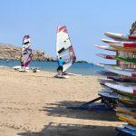 Kaksi miestä säätää purjelautoja aurinkoisella hiekkarannalla.
