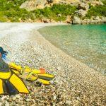 Keltaiset räpylät, uimalasit ja snorkkeli sileäkivisellä rannalla.