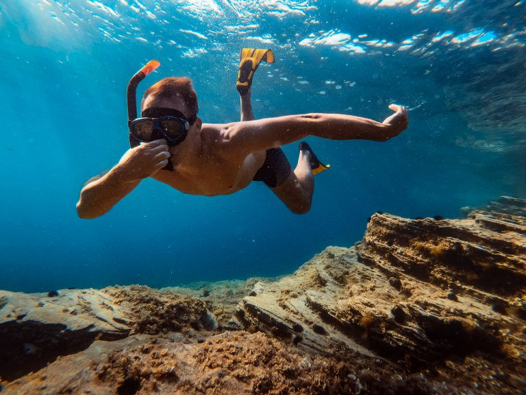 Mies ui veden alla räpylät jalassa ja pitää nenästä kiinni.