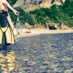 Nainen seisoo rantavedessä uimaräpylät, uimalasit ja snorkkeli käsissään.