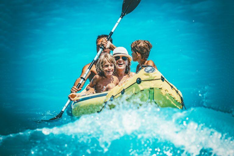 Iloinen perhe keltaisessa kumiveneessä.
