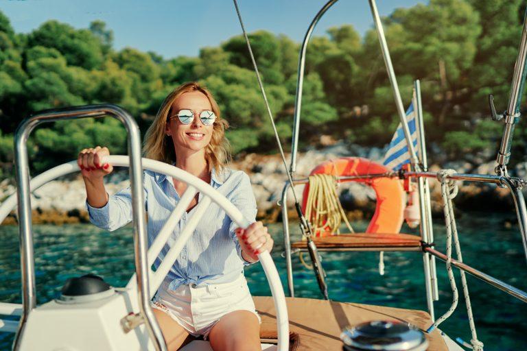 Aurinkolasipäinen nainen pitää kiinni veneen ohjauspyörästä ja hymyilee.