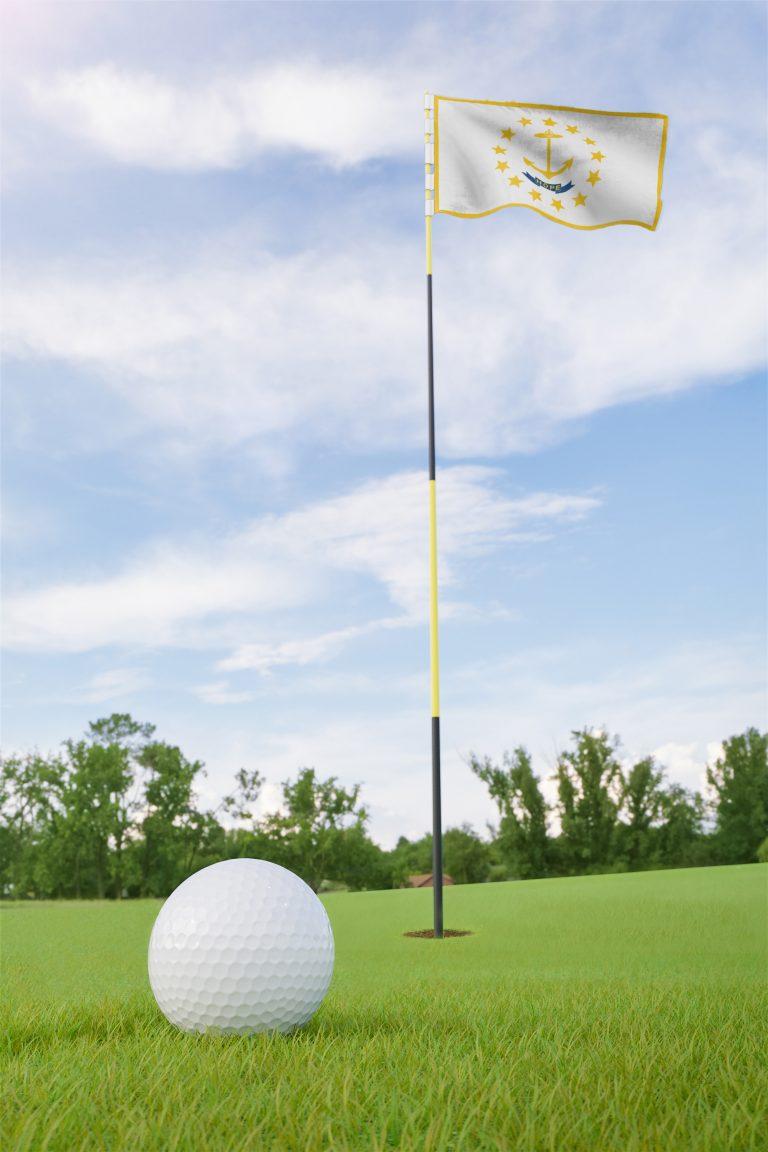 Lähikuvassa golfpallo viheriöllä, taustalla lipulla merkitty reikä.