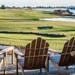 Näkymä terassilta tuoliryhmän takaa golfviheriölle.