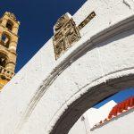 Panagian kirkon valkoinen kaari, jonka takaa näkyy korkea torni.