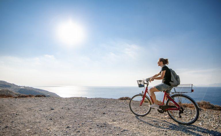 Nuori nainen punaisen pyörän selässä aurinkoisena päivänä mäen päällä.