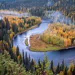 Joki mutkittelee ruskaisen metsän keskellä.
