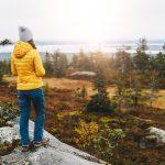 Pipopäinen, keltatakkinen nainen seisoo tunturilla kiven päällä ja katsoo maisemaa.