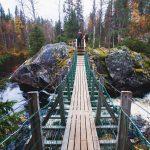 Kaksi retkeilijää rinkat selassa kosken ylittävän sillan toisella puolella Kuusamossa.