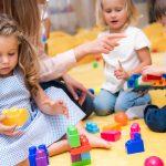 Kolme pientä lasta rakentaa värikkäillä palikoilla aikuisen neuvoessa.