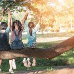 Kolme tyttöä istuu paksun puun oksan päällä kädet ilmassa.