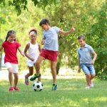 Neljä iloista lasta pelaa jalkapalloa puistossa.