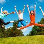 Neljä lasta hyppäämässä ilmaan riemukkaat ilmeet kasvoillaan.