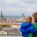 Äiti katsomassa Riikaa kattotasanteella pieni poika sylissään.
