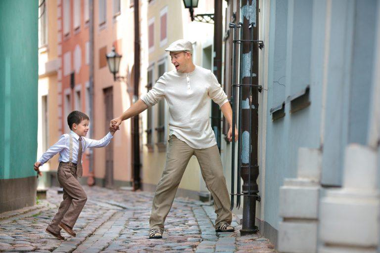 Vanhaan tyyliin pukeutunut hypähtämässä oleva poika pitää isäänsä kädestä kapealla kujalla Riiassa.
