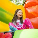 Tyttö istuu nauraen värikkäässä pomppulinnassa.
