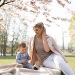 Nuori äiti katsoo pientä lastaan kirsikkapuun alla puistossa.