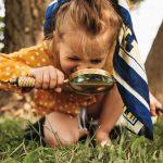 Polvillaan oleva pieni lapsi tutkii nurmikkoa suurennuslasilla.